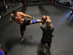 As other coaches watch in the cage and fighters and children watch in the background, heavyweight Frank Mir, left, works out in a private gym in Las Vegas with Muay Thai coach Shawn Yarborough in preparation for UFC 130.