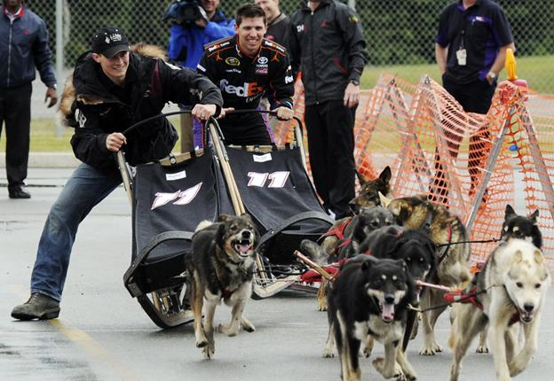Iditarod champion Dallas Seavey, left, slides his dog team past Denny Hamlin at the FedEx Express Hub in Anchorage on June 25. Hamlin and sponsor FedEx are expected to sign a long-term deal next week.
