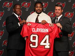 Buccaneers first round draft pick Adrian Clayborn (middle) holds up his jersey with head coach Raheem Morris (left) and general manager Mark Dominik after he was introduced Friday.