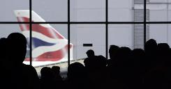 A British Airways aircraft is pictured as passengers queue at London's Heathrow airport.