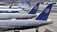 United Airlines planes, including two Boeing 747s, rear, and two 777s, front, sit on the tarmac at San Francisco International Airport.