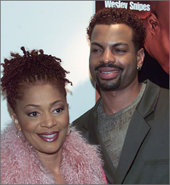 In happier times: Author Terry McMillan, seen here with then-husband Jonathan Plummer, is suing him on grounds he tried to ruin her reputation during their divorce.