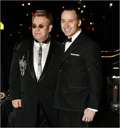 Saturday night's all right for partyin': Elton John, left, and partner David Furnish arrive at John's birthday party in New York.
