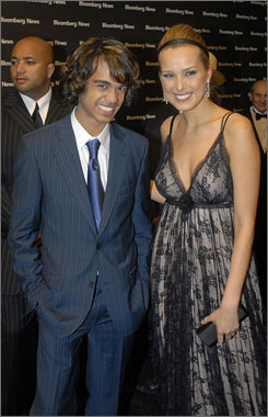 Blue pinstripes, loose curls: Sanjaya Malakar arrives at the Bloomberg News after-party with model Petra Nemcova.