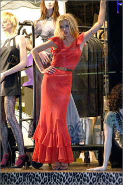 Big hit in England: Kate Moss models a dress from her collection in a Topshop store window in London during the line's launch April 30.