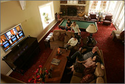 """A healthy home: Loveline's Dr. Drew Pinsky and his wife, Susan, watch TV with triplets Jordan, left, Paulina and Douglas, 14. The sideboard holding the TV is a family heirloom from Susan's grandmother. """"She always told me to buy furniture of substance, made from good wood,"""" Susan says."""