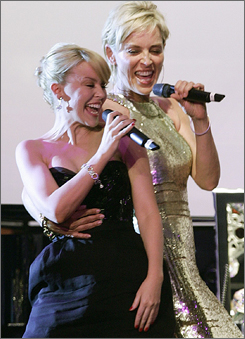Kylie Minogue, left, and Sharon Stone sing for their fellow celebs at the amfAR Cinema Against AIDS soiree in Cannes.