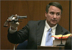Los Angeles sheriff's Detective Mark Lillienfeld displays the Colt revolver found near Lana Clarkson's body at the crime scene during the Phil Spector trial in Los Angeles  County Tuesday.