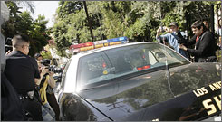 A squad car takes Paris Hilton to a Friday court hearing in Los Angeles, where a judge ordered her back to jail.