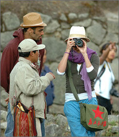 Cameron Diaz, right, snaps photos while wearing the infamous bag during a tour of Inca ruins of Machu Picchu near Cuzco, Peru, Friday.