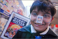 A Harry Potter fan from Fircroft Primary School, dressed in his best wizard wardrobe, displays one of the new Potter stamps Tuesday in London.