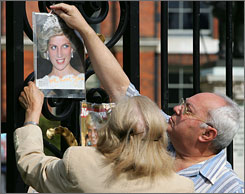 """Remembering """"People's Princess"""": A couple hang a photo on the Kensington Palace gates in honor of the 10th anniversary of Diana's death in a car accident."""