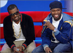 Kanye West, left, and 50 Cent were on BET's 106 & Park last week. It's not official yet, but it looks like West might beat 50 in their sales slugfest.