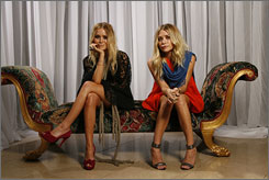 Designing women: Mary-Kate, left, and Ashley Olsen model the lace caftan and tangerine parachute dresses from their new clothing line, Elizabeth & James.