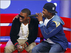 Rappers Kanye West, left, and 50 Cent share a laugh on BET's 106 & Park in September.