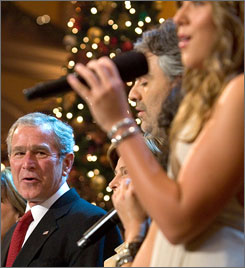 President Bush sings along with singer Andrea Bocelli, center, and Colbie Caillat.