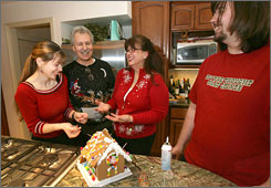 Gingerbread and joy: Alexa Portney, left, dad Kent Portney, mom Marilyn Santiesteban and brother Teddy prepare for the family's Christmas Eve celebration. For the past 15 years or so, the family has served roast pig and fried plantains to 50 to 60 friends and neighbors.