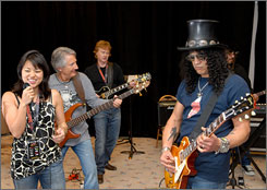 Living the dream: As part of the Rock 'n' Roll Fantasy Camp in Las Vegas, Hyun-Joo Park, left, Vaughan Merlyn on bass and Hugh Riddell on guitar get a session with Slash of Guns N' Roses fame.
