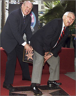Johnnny Grant, right, hands football commentator Terry Bradshaw his Walk of Fame plaque in an appropriate fashion in 2001. Grant, known as the honorary mayor of Hollywood, died Wednesday.