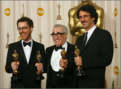 Ethan Coen, left, and Joel Coen pose with Oscar-winning director Martin Scorsese, center, after their Academy Award wins.