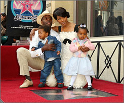Angela Bassett poses in front of her new star with husband Courtney B. Vance and their children.
