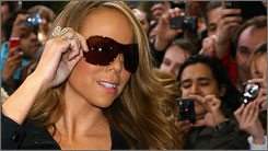 Mariah Carey signs copies of her new single Touch My Body Monday in London.