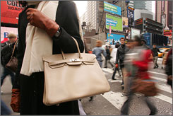 A passing glance: Reporter Kelly Carter walks near Times Square in New York with a $9,000 Birkin handbag made by Herms.