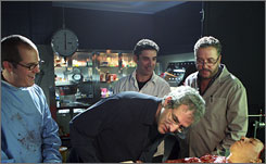 Close inspection: Men's Lee Aronsohn, front, investigates the autopsy room with CSI's David Berman, left, Men's Chuck Lorre and CSI's William Petersen.