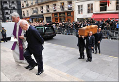 Yves Saint-Laurent's partner, Pierre Berge, and Father Roland Letteron enter the Saint-Roch church in Paris followed by pallbearers carrying Saint Laurent's coffin.