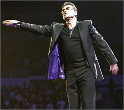 George Michael extends the microphone to his audience during a concert in San Diego on Tuesday.