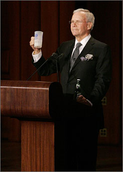 Here's to you, Tim: Tom Brokaw of NBC News hoists a beer mug given to him by Tim Russert's dad at Wednesday's memorial service at the Kennedy Center.