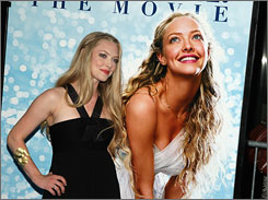 Twice as nice: Amanda Seyfried, left, stopped under a poster featuring  a picture of herself at Wednesday's American premiere of Mamma  Mia! The film opens nationwide on Friday.