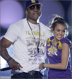 Host Miley Cyrus teams up with rap veteran LL Cool J onstage at Sunday's Teen Choice Awards.