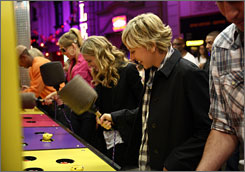 Whack-A-Mole: Ellen DeGeneres plays with Nick Cannon, left, Mariah Carey and Portia de Rossi.