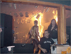 In this photo from Feb. 20, 2003, Scott Vieira, right front, and Daniel Biechele, right, tour manager for the band Great White, appear near the stage in the Station nightclub in West Warwick, R.I., as foam behind the stage bursts into flames. One hundred people died in the fire.