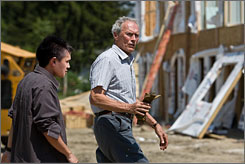 "Life lessons: Bee Vang, left, plays the teenage immigrant whom Clint Eastwood tries to help out in Gran Torino. ""Walt helps him get a job and helps him toughen up a bit,"" Eastwood says, noting the image at the construction site. Walt ""doesn't work construction. He's retired. But he gets the boy in through a buddy, an old crony. They take him in and try to show him how to handle himself in life."""