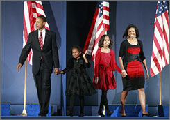 Barack Obama leads his family onstage during his election night victory rally in Chicago. Obama holds daughter Sasha's hand, as Mailia and his wife Michelle Obama follow.