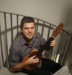 El jefe: Gustavo Santaolalla, up for multiple Latin Grammys on Thursday, plays a ronroco in his Los Angeles studio. Santaolalla is a musical artist, producer, film composer and pioneer of the rock en Espanol movement.