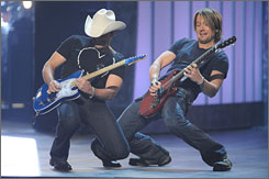 Brad Paisley, left, and Keith Urban kick off the CMA Awards with their dueling duet, Start a Band, the first single from Paisley's new album, Play.