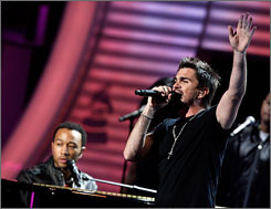 Latin Grammy winner Juanes performs with R&B star John Legend, sitting at the piano.