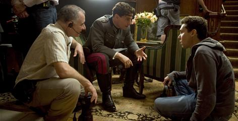 Valkyrie director Bryan Singer, right, works on a scene with Tom Cruise, center, and photography director Newton Thomas Sigel.