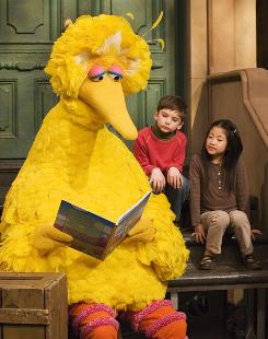 Big Bird reads to Connor Scott and Tiffany Jiao on Sesame Street in April. The show is marking its 40th anniversary in 2009.