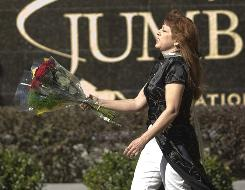 Sherie Maud, of Ocala, Fla., brings a bouquet of roses to Thursday's memorial service for Jett Travolta.