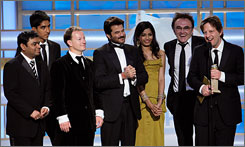 The Slumdog Millionaire cast and crew celebrate their Golden Globe for best drama. The movie returns home to Mumbai next week for its Indian debut.