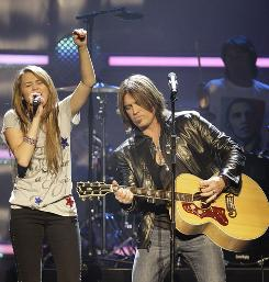 Miley Cyrus teams up with her dad, Billy Ray Cyrus, on stage at the Kids' Inaugural: We Are the Future concert at the Verizon Center in Washington. Fellow Disney stars the Jonas Brothers, Demi Lovato and Corbin Bleu also were there.
