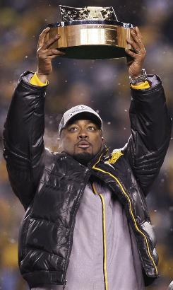Pittsburgh coach Mike Tomlin holds up the championship trophy after his Steelers beat the Baltimore Ravens 23-14 in the Steel City to advance to the Super Bowl.