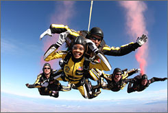 "Miss U.S.A. Crystal Stewart experiences her first free fall riding with tandem instructor Sgt. 1st Class Mike Elliott and other members of the U.S. Army Parachute Team ""Golden Knights"" at Yuma Proving Grounds, Ariz. on Monday."