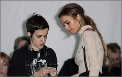 Lindsay Lohan talks to DJ Samantha Ronson before the Charlotte Ronson collection show at New York Fashion Week on Friday.