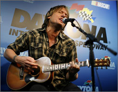 Keith Urban performs during a news conference before the start of the Daytona 500 on Sunday.