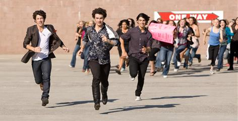 Fans give chase to Nick, left, Kevin and Joe in Jonas Brothers: The 3D Concert Experience. The film, which arrives Feb. 27, gives a nod to The Beatles' Hard Day's Night, one of the brothers' favorite films.